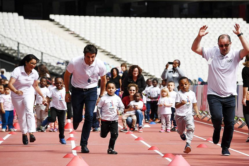 Patrick Baumann (right), head of the 2024 Olympic Games evaluation panel, and co-president of the Paris bid Tony Estanguet running with children at the Stade de France.