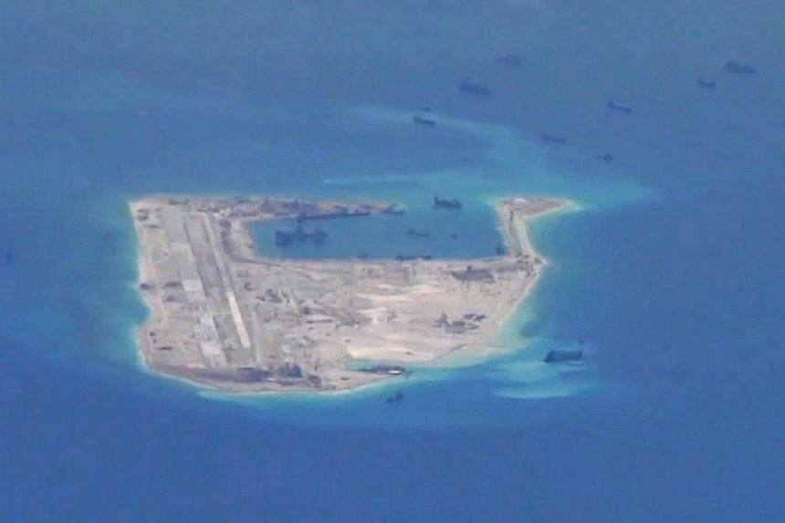Chinese dredging vessels are purportedly seen in the waters around Fiery Cross Reef in the disputed Spratly Islands in the South China Sea in this still image from video taken by a P-8A Poseidon surveillance aircraft provided by the United States Nav