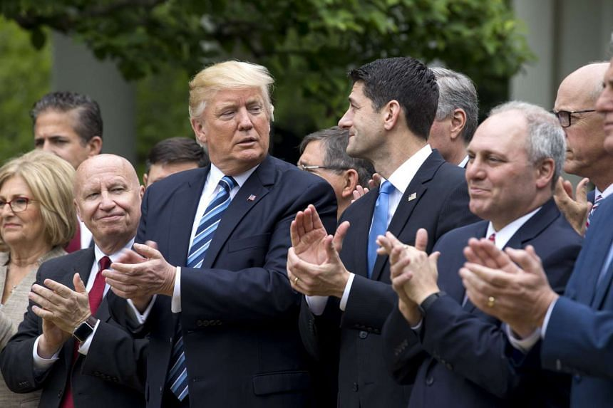 President Donald Trump  and Republican Speaker of the House from Wisconsin Paul Ryan (centre-right), along with GOP lawmakers, in the Rose Garden of the White House in Washington, DC, USA, on May 4, 2017.