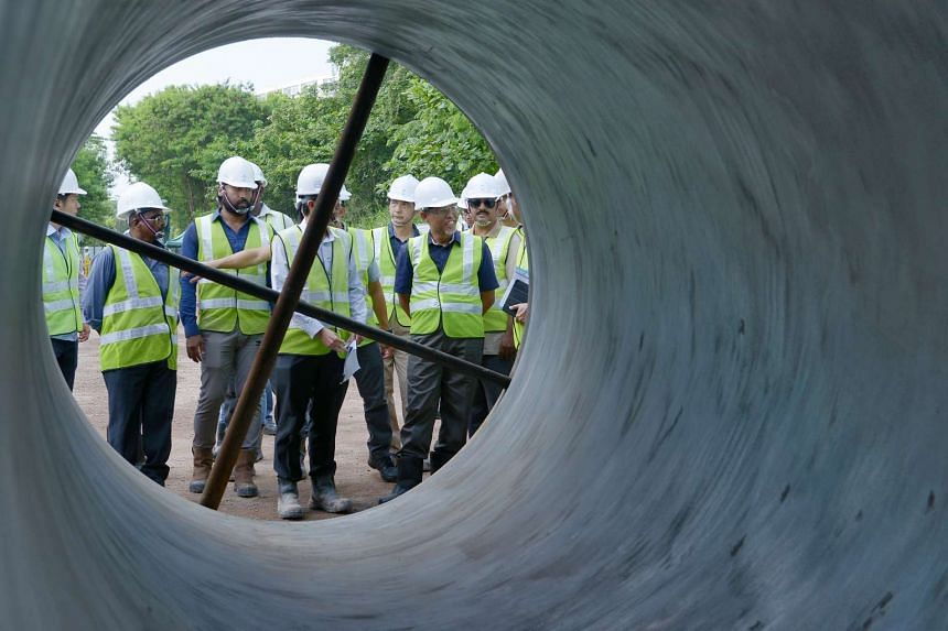 Minister for Environment and Water Resources, Mr Masagos Zulkifli (second from right) inspecting a water pipe at the Tanglin Halt Road pipeline construction site.