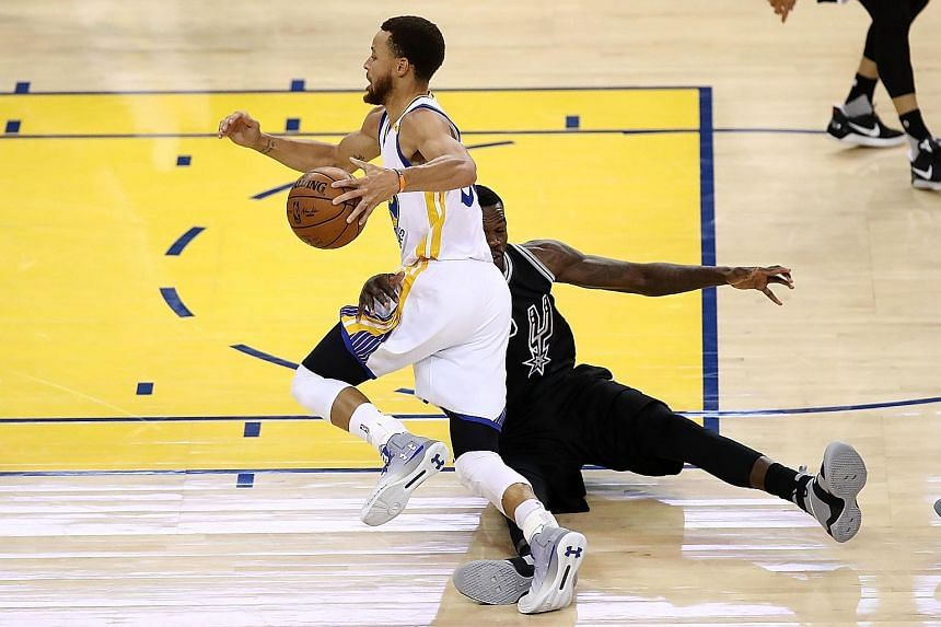 San Antonio's Dewayne Dedmon trying, but failing to stop Golden State's Stephen Curry driving past him. The Warriors guard was hard to handle on a night when he hit 15 points in 12 first-quarter minutes