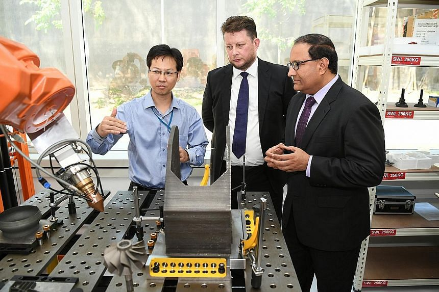 Chief executive officer of 3D Metalforge, Mr Matthew Waterhouse, and Minister for Trade and Industry (Industry) S. Iswaran yesterday during a tour of the facility, which will make parts for the marine and offshore, oil and gas, manufacturing, enginee