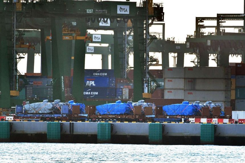 Nine SAF Terrex Infantry Carrier Vehicles, covered with tarpaulins, on the wharf at the PSA Pasir Panjang terminal as seen from Labrador Jetty.