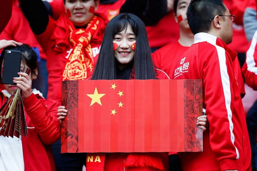 A fan holds a Chinese national flag inside Helong Stadium ahead of a 2018 FIFA World Cup qualifier match between China and South Korea in Changsha, Hunan province, China, March 23, 2017.