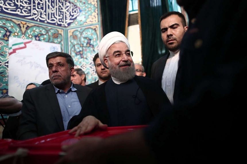 Iranian President and presidential candidate, Hassan Rouhani, casts his ballot for the presidential elections at a polling station in Tehran on May 19, 2017.