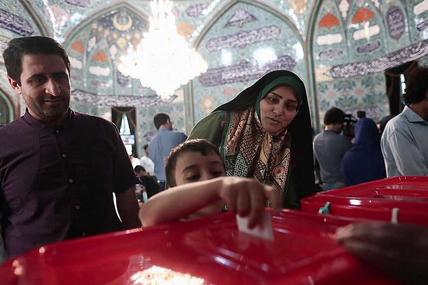 An Iranian boy casting his mother's ballot for the presidential election in Teheran yesterday. People queued in temperatures topping 32 deg C to vote. Shortly before polls were due to close, state television reported that voting was extended by at le