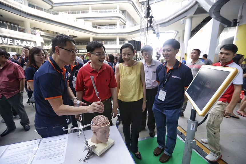 Mr Heng Swee Keat touring a booth that exhibits a neurosurgical navigation system during the National Neuroscience Institute Brain Awareness Carnival at Our Tampines Hub on May 20.