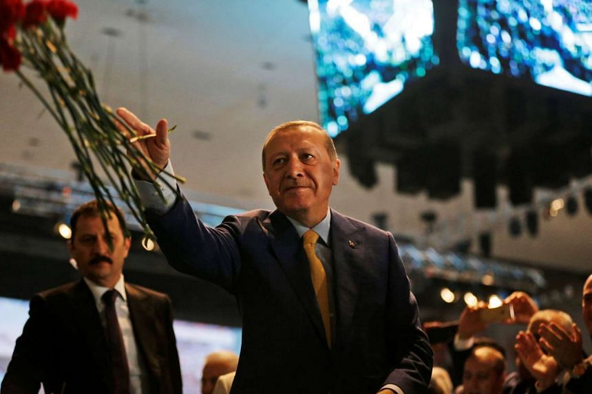 Turkey's President Tayyip Erdogan throws flowers to supporters as he arrives for a congress of the ruling Justice and Development Party in Ankara, on May 21, 2017.