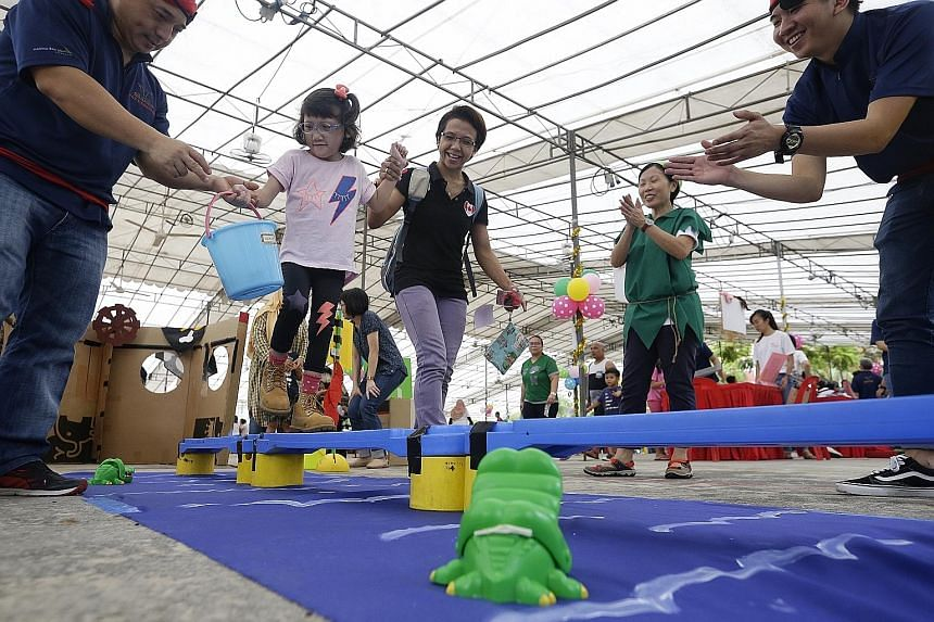 Arianna Azmi - who has a rare chromosome disorder that affects her physical development - making her way across a balance beam with the help of her mother, Madam Sara Handayani, during World Play Day at Pasir Ris Elias Community Club yesterday.