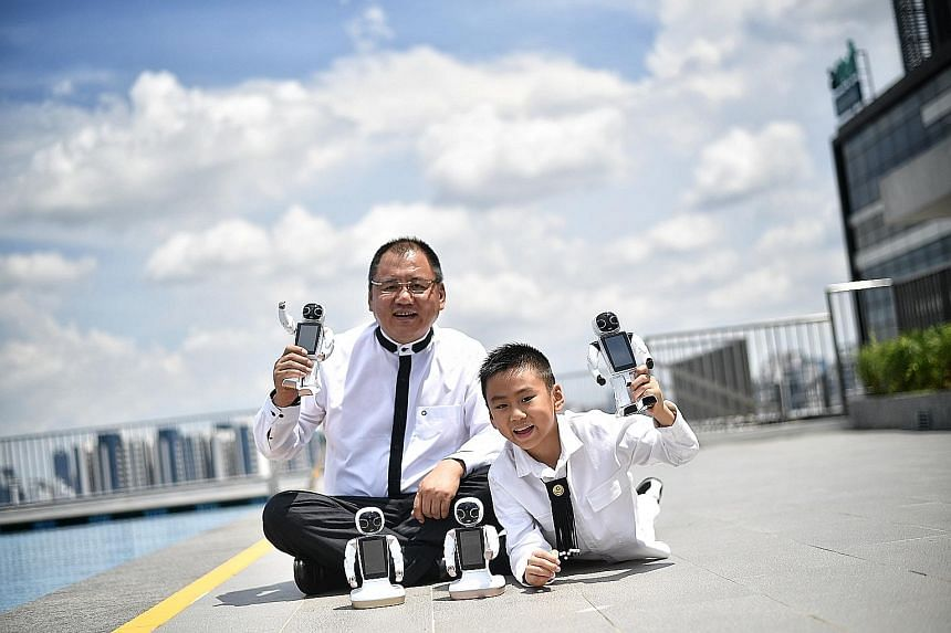 Dr Paul Zhang and his son Emiliano with the 24cm-tall GT Wonder Boy. The robot can converse in 13 languages, recognise voices and faces, do mathematics, dance and sing. And it can also do what a regular smartphone does, including taking photos.