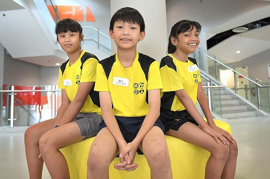 (From left) Meagan Lim, 12, Isaac Ong, 11 and Amirah Fikriyah Herman, 11, were among the first cohort of students under the revised Junior Sports Academy (JSA) programme to graduate yesterday.