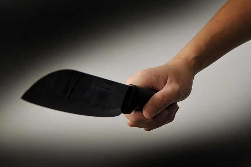 Posed photo of a person holding a knife.
