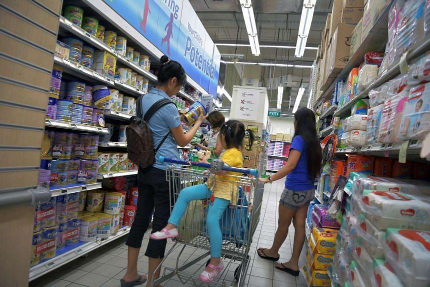 A lady buying milk powder at the Fairprice Xtra outlet at Ang Mo Kio Hub on May 11, 2017.