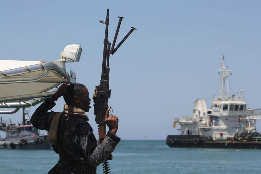 A maritime policeman on a tag-boat guards oil tanker Aris-13, which was released by pirates, as it sails to dock on the shores of the Gulf of Aden in the city of Bosasso, northern Somalia's semi-autonomous region of Puntland, on March 19, 2017.