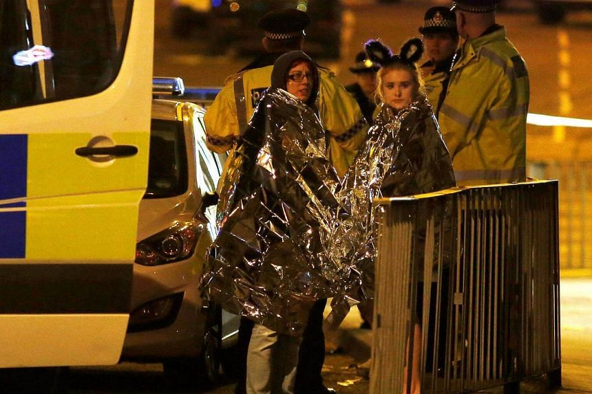 Concert goers react after fleeing the Manchester Arena in northern England on May 22, 2017.
