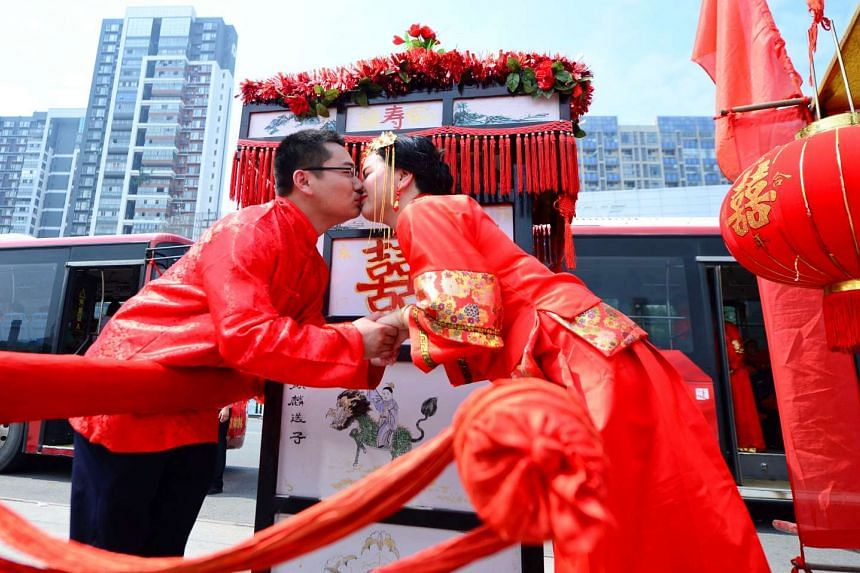 A newlywed couple kisses during wedding ceremony in traditional Han Dynasty style in Ganzhou, Jiangxi province, on China's Valentine's day, on May 20, 2017.
