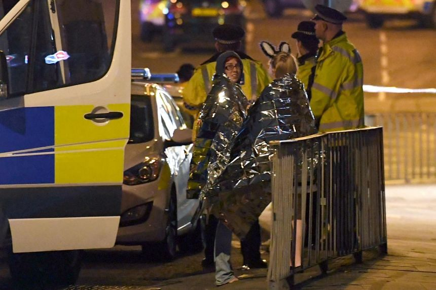 Concert goers waiting to be picked up at the scene of the explosion during a pop concert by US star Ariana Grande in Manchester, northwest England on May 23, 2017.