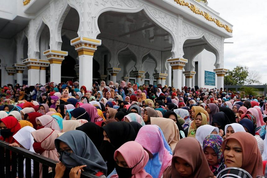Indonesian women stand in front of the Syuhada mosque as they watch a man being publicly caned for having gay sex, in Banda Aceh, Aceh province, Indonesia on May 23, 2017.