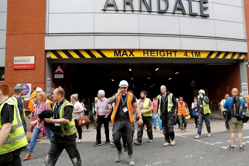 People rush out of the Arndale shopping centre as it is evacuated in Manchester, Britain on May 23, 2017.