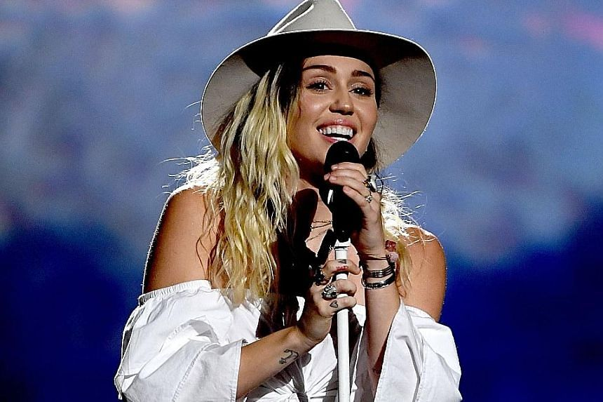 Miley Cyrus (above) returned to her country roots with a pared-down performance of Malibu, while Celine Dion struggled to hold back her tears when she performed My Heart Will Go On.