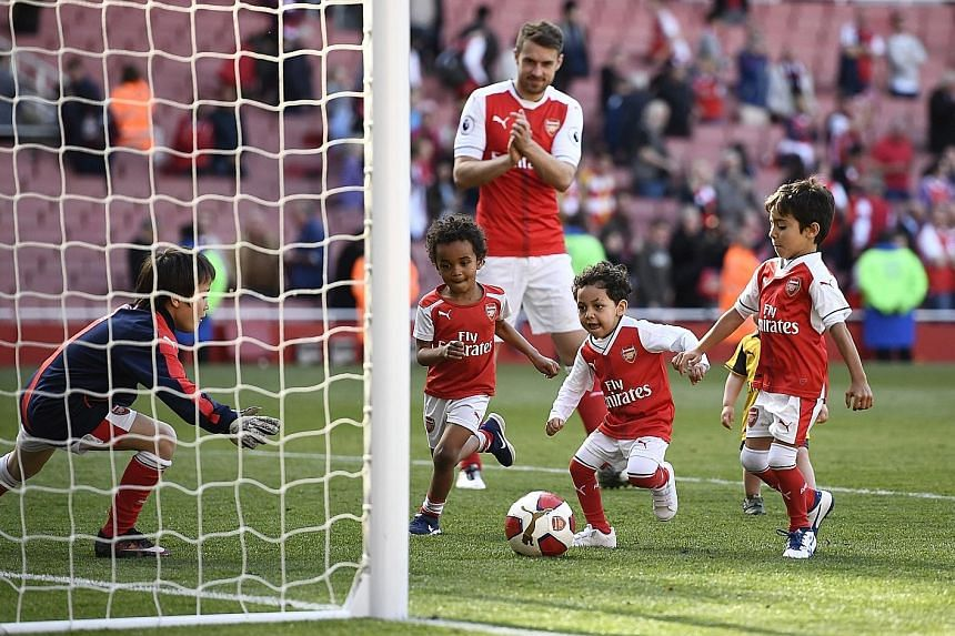 Arsenal's Aaron Ramsey watching some of his team-mates' children play on the Emirates pitch during the traditional end-of-season lap of appreciation with players and their family. The Emirates supporters will have to get used to navigating the unchar