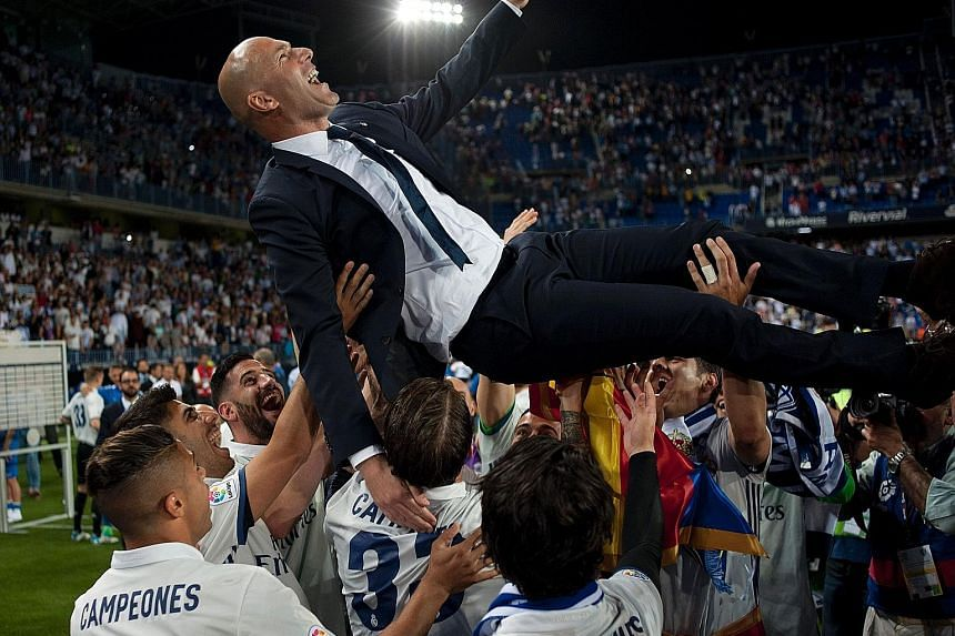 Real Madrid coach Zinedine Zidane is hoisted in the air by his players after a 2-0 win over Malaga sealed their 33rd La Liga crown, three points clear of rivals Barcelona.