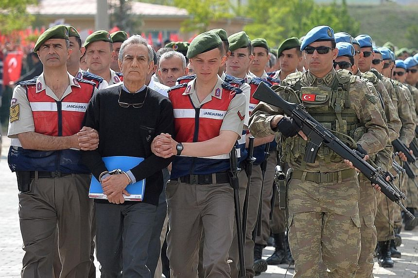 Former air force chief Akin Ozturk, the most prominent figure among the accused, being escorted by Turkish security forces as he arrives at the court outside Ankara yesterday. Heavy security was in place as the accused were paraded into court.