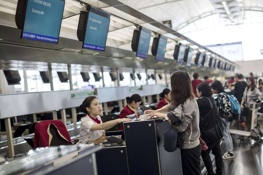 A Cathay Pacific employee checks-in a passenger in Hong Kong International Airport, on May 22, 2017.