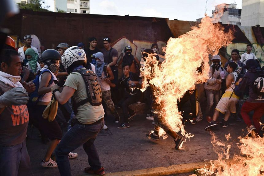 Demonstrators set a young man on fire during an anti-government protest in Caracas on May 20, 2017.