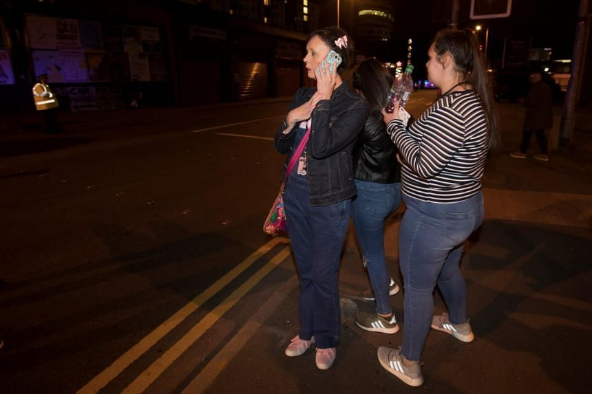 Concert-goers react after fleeing the Manchester Arena, on May 22, 2017.