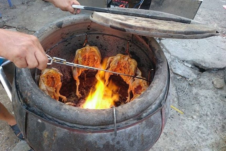 Chickens being grilled in a claypot, with charcoal burning at the bottom of the pot. PHOTO: VIETNAM NEWS