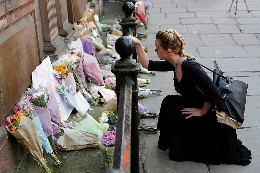 A woman laying flowers for the victims of the Manchester Arena attack in central Manchester yesterday.