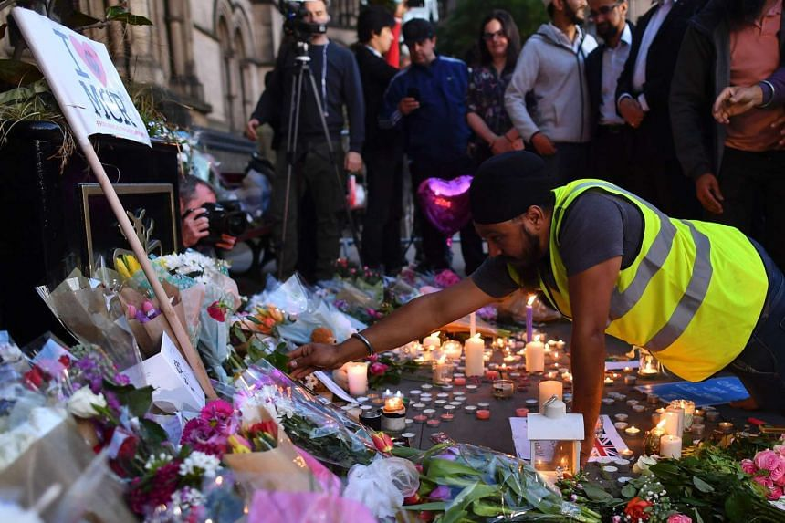 A man adding a single rose to the messages and floral tributes in Albert Square in Manchester, on May 23, 2017