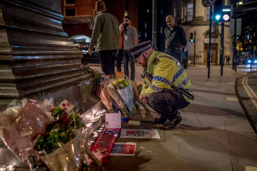A policeman visiting a makeshift memorial to victims of the Manchester Arena bombing, on May 23, 2017.