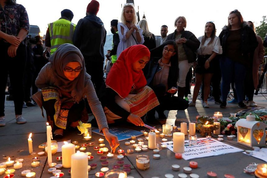 Women lighting candles following a vigil in central Manchester, on May 23, 2017.