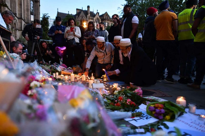 People lighting candles set up in front of floral tributes in Albert Square in Manchester, on May 23, 2017.
