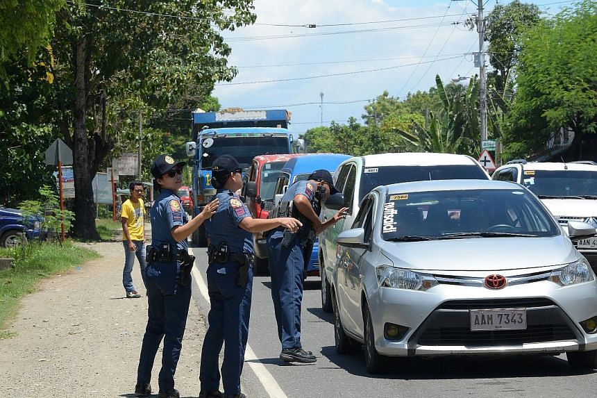 A police checkpoint set up along a highway yesterday in Iligan City, Mindanao. The southern island group of Mindanao is home to some 20 million Filipinos. Residents fleeing Marawi City yesterday after militants mounted attacks, torching buildings, be