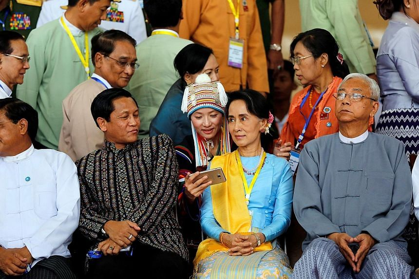An ethnic woman tries to take selfie with Myanmar's Aung San Suu Kyi after the opening ceremony of the peace conference, the second round of peace talks since her civilian government came to power. Flanking her are Myanmar President Htin Kya (right)