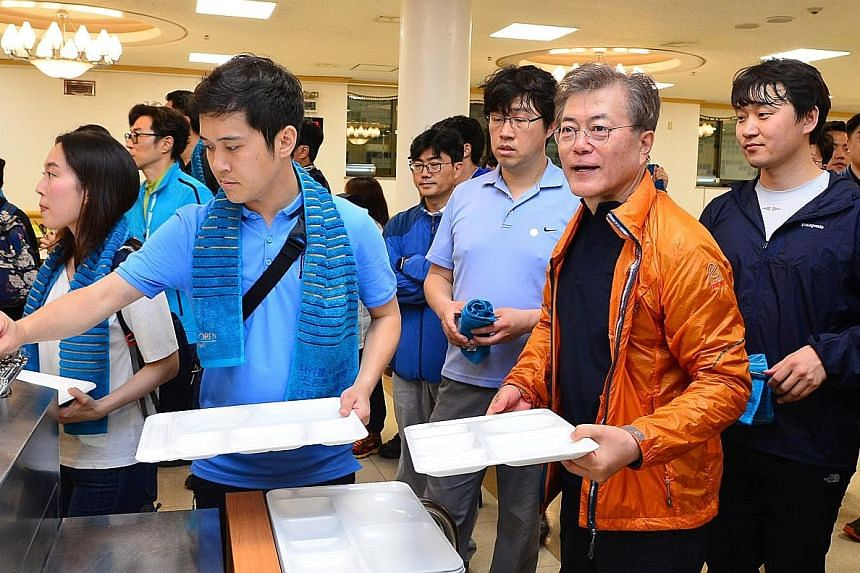 Airport employees taking selfies with Mr Moon at the Incheon International Airport in Seoul last week. Mr Moon's popularity is at a peak, with 87 per cent of respondents in a Gallup poll positive about the outlook for his performance. South Korean Pr