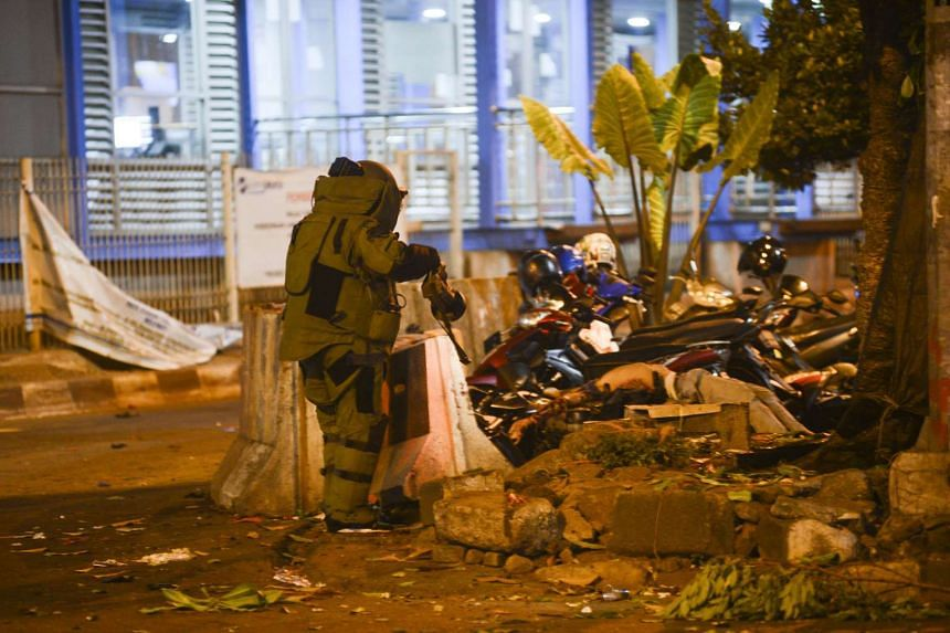 An Indonesian bomb squad police officer searches for explosives near a body in Jakarta.