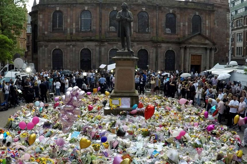 Crowds look at the balloons, flowers and messages of condolence left for the victims of the Manchester Arena attack, in central Manchester, Britain on May 25, 2017.