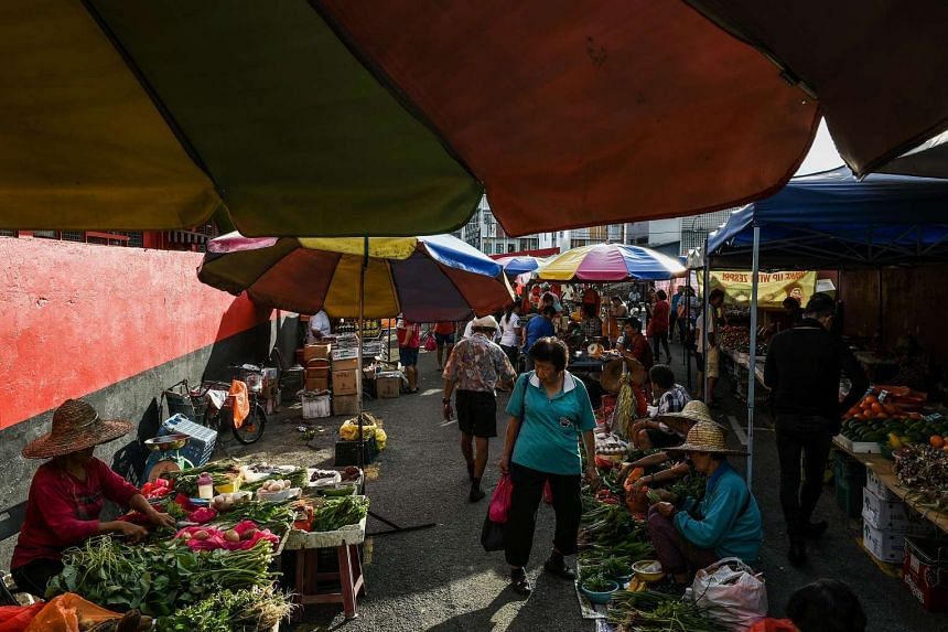 Malaysians shop for vegetables along a lane beside a wet market in Bentong on April 5, 2017.