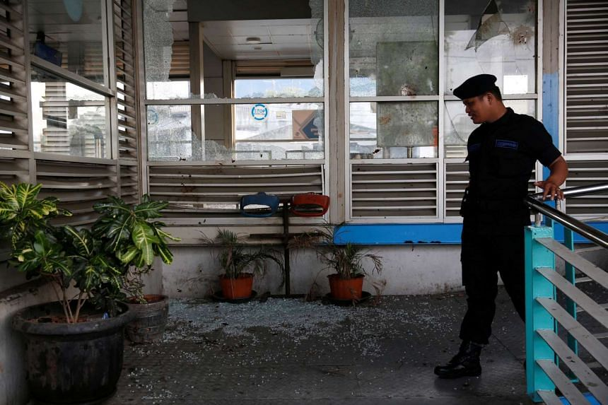 A security officer walking near the scene of an explosion at a bus station in Kampung Melayu, Jakarta, on May 25, 2017.