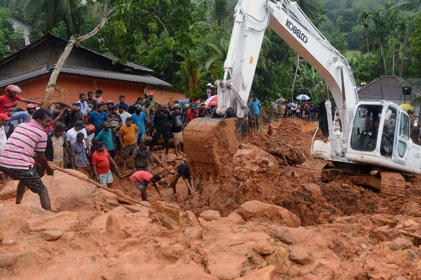 Sri Lankan military rescue workers and villagers search for survivors at the site of a mudslide in Bellana village in Kalutara on May 26, 2017.