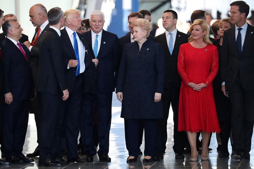 US President Donald Trump adjusts his jacket after pushing past Montenegro Prime Minister Dusko Markovic at the NATO Summit in Brussels, Belgium on May 25, 2017.