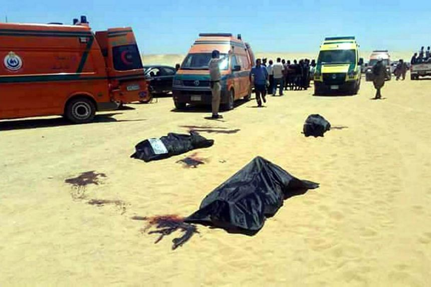 Security officials and emergency services at the site of an armed attack on a bus near the Monastery of St Samuel the Confessor, in Minya Province, central Egypt, on May 26, 2017.