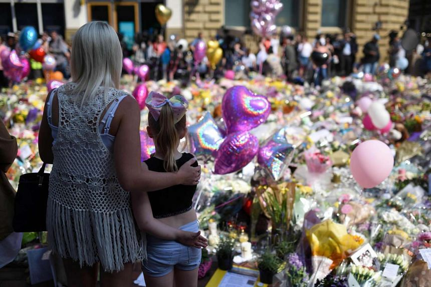 People gather to see flowers and messages of support in St Ann's Square in Manchester, northwest England on May 25, 2017, placed in tribute to the victims of the May 22 terror attack at the Manchester Arena.