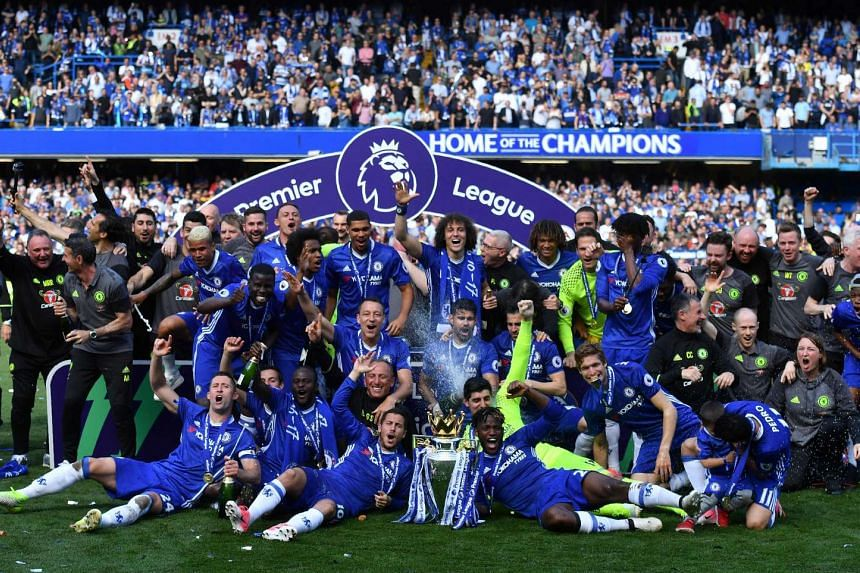 Chelsea's players gather on the pitch with the English Premier League trophy, as players celebrate their league title win at Stamford Bridge in London on May 21, 2017.