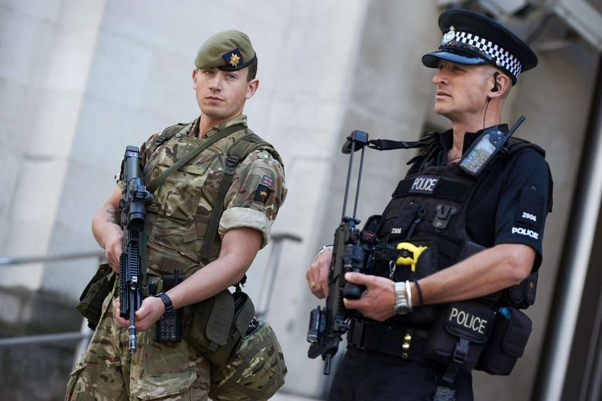 A British army soldier (left) and a police officer secure an entrance to the Ministry of Defence in central London.