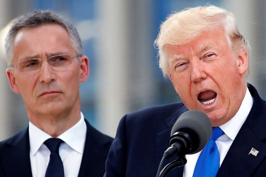 Trump (right) speaks beside Nato chief Stoltenberg at the start of the Nato summit.
